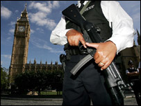 An armed police officer carries his weapon on gate duty outside the Palace of Westminster