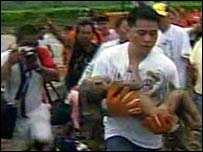 A child is carried from the scene of the landslide in Southern Leyte, Philippines