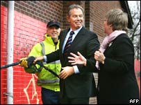 Tony Blair removes graffiti at a community project