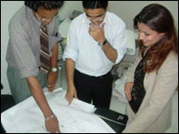 Fatima al-Attar looks at design plans with two colleagues
