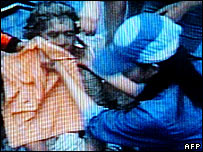In this television grab shows a Philippines villager (R) comforting a victim after a landslide that covered an entire village in Leyte, 17 February 2006