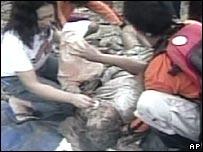 Philippines villagers comfort a victim