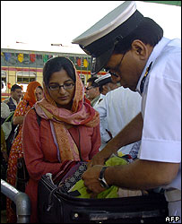 A Pakistani customs officer checks the luggage of a Pakistani passenger at a station on the Indo-Pakistan border