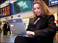 Woman using a laptop in a railway station