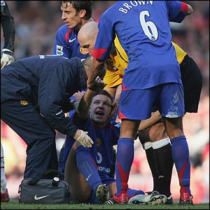 The club doctor tends to Alan Smith on the pitch as Gary Neville and Wes Brown surround him