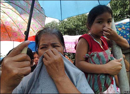Villagers cover their noses at a temporary morgue in southern Leyte