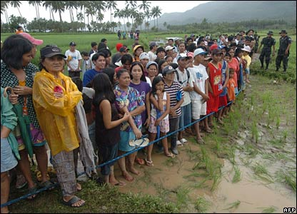 Villagers wait at a cordon near the site of the mudslide