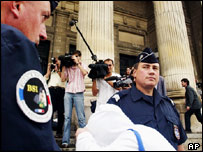 An unidentified defendant hides his face as he arrives outside the Angers courthouse