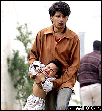 Man carries child overcome by teargas fumes during protest in Islamabad