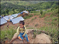 A young ethnic Hmong refugee sits along a roadside in Phetchabun province in north-eastern Thailand, 10 July 2005