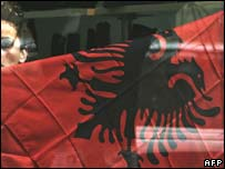 A woman in a shop in Pristina displaying the Albanian flag