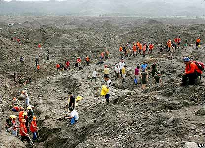 Rescuers dig up earth to search for victims at the site Monday Feb. 20, 2006 where an elementary school is believed buried in a massive landslide