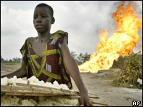 Nigerian youth standing before burning oil facility