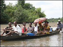 A boat taxi on Iko Creek. Colourful umbrellas shade passengers from the sun.