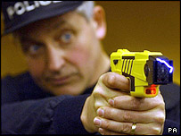 A policeman using a Taser gun