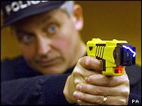A policeman using a Taser gun