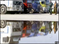 Harbour workers walks past a row of trucks in the port of Piraeus, near Athens