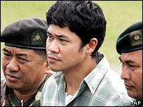 Filipino fugitive first Lieutenant Lawrence San Juan, centre, walks with army escorts as he alights from a Huey helicopter at army headquarters in suburban Manila on Tuesday Feb. 21, 2006.