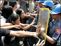 Philippine anti-riot police push back student protesters as they block a busy street to call for the ouster of Philippine President Gloria Macapagal Arroyo in Manila on Tuesday, Feb. 21, 2006