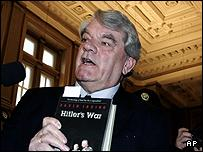 "British historian David Irving holds his book 'Hitler""s War"" when arriving at a court in Vienna"