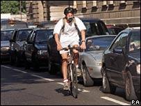 Man cycling past traffic congestion