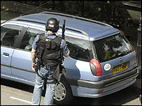 An armed police officer during raids in Notting Hill, London