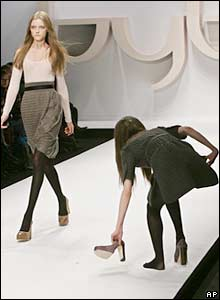A model recovers a dropped shoe