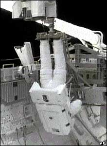 Steve Robinson hangs suspended from robotic arm (pictures from Nasa TV)