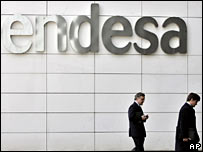 Businessmen walk past the Spanish electricity company headquarters Endesa in Madrid