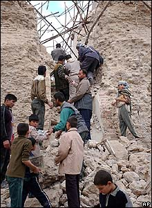 Iraqis search the rubble of the bomb site