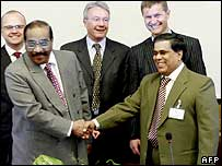Tamil Tiger negotiator Anton Balasingham (left) and  Sri Lankan representative Nimal Siripala de Silva (right) shake hands