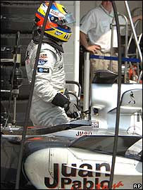 Juan Pablo Montoya climbs out of his car after retiring from the lead