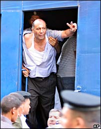 An Egyptian pro-reform activist gestures from a police truck as he is arrested