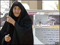 An Iraqi woman walks past posters informing the public about the new constitution