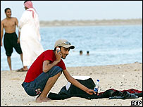 Young Saudi man on a beach, talking into a mobile phone