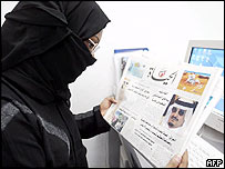 Saudi woman reading a newspaper detailing health problems of King Fahd