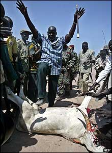 John Garang with a slaughtered cow