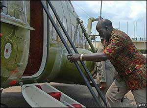 John Garang climbs into the Ugandan presidential helicopter