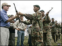 Peace Commissioner Luis Carlos Restrepo (L) receives a rifle from a paramilitary fighter in San Pablo, northern Colombia