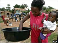 Woman filling in her ballot paper, while carrying a child