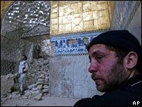 Iraqi man sits in rubble of shrine in Samarra