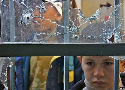 Iraqi children look from a bullet-riddled window of Abu Ayoub al-Ansari mosque in the city of Baquba