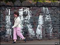 Woman walks past IRA painted on a stone wall