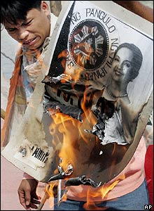 A protester burns a picture of President Arroyo