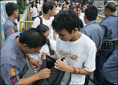 Policemen inspect students' bags outside the presidential palace