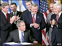 President George W Bush signs up to Cafta, surrounded by senators and Central American representatives