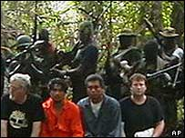 The hostages with armed men behind them