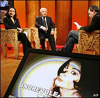 Vladimir Luxuria (seated on left and on poster) in a TV debate