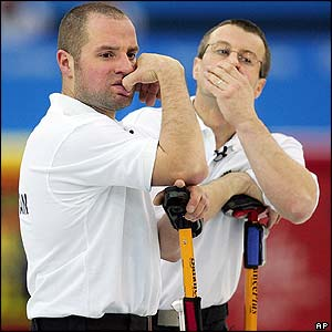 Great Britain curlers Euan Byers and Warwick Smith look on anxiously