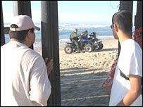 Antonio Ortega looks at a US border patrol through the gap in the barrier